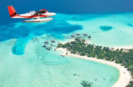 Seaplane flying above Maldives island